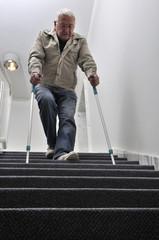 Senior mit Krücken auf einer Treppe