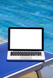 Laptop by swimming pool and tropical vacation resort