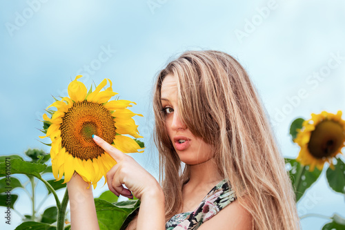 young beautiful woman between sunflowers
