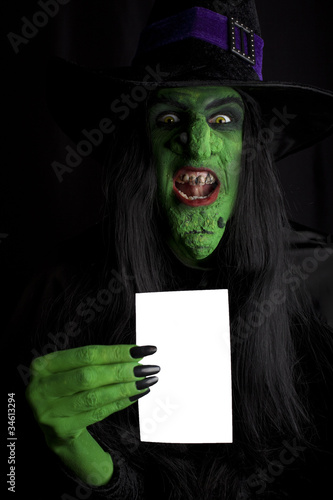 Scary green witch with space for text, black background.