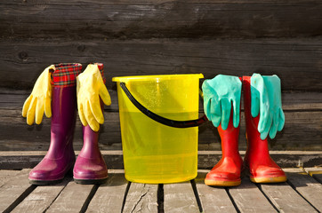 Bucket,rubber gloves and pairs of rubber boots at veranda