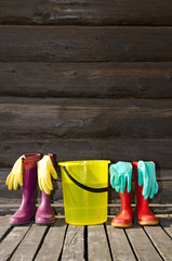 Two pairs of rubber boots, bucket and gloves on veranda