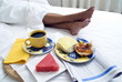 Füsse neben einem Frühstückstablett