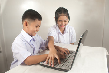 Happy boy and girl using computer.