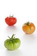 Three fresh tomatoes (red, orange and green)