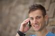 lächelnder junger Mann an einer Mauer mit Smartphone
