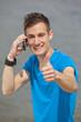 lächelnder junger Mann mit Mobiltelefon zeigt Daumen hoch