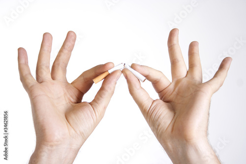 Man's hands breaking a cigarette