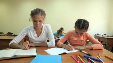 Young school teacher checking her pupil's work
