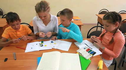 Three pupils modeling plasticine figures with their teacher