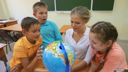 Three pupils spinning a globe with their teacher