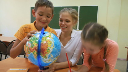 Two pupils examining globe with their teacher
