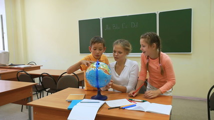 Two pupils and their teacher looking at globe in classro