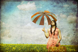 Brunette enchantress with umbrella and suitcase at spring rapese