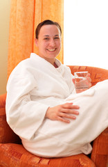 Young woman in bathrobe holding glass of water