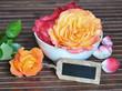 Arrangement mit Rosen und kleiner Tafel