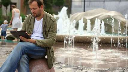man with tablet computer sitting by the fountain, slow motion