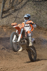 Motocross rider on a motorcycle rides on the rear wheel