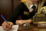 Young Woman Hotel Receptionist At The Front Desk - 34653220