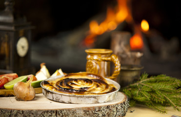 Meat Pie on a Rustic Wooden Tray in Front of the Fireplace