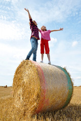 children standing on a bale of straw