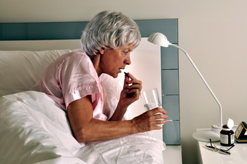 Ältere Frau nimmt  eine Tablette im Bett