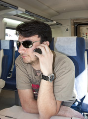 An Adult Man with Smartphone using Wireless Network on Train