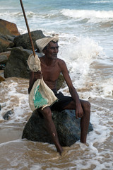 The old man from sri lanka sits on the shore of the ocean