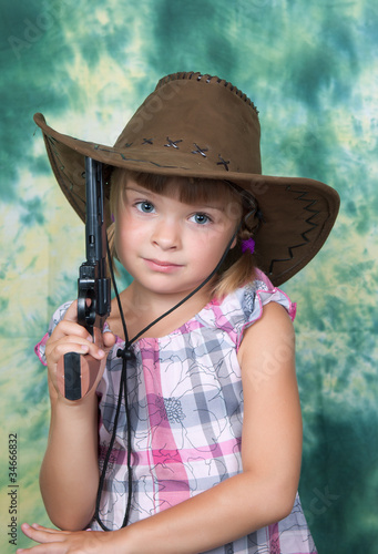 Portrait of a beautiful girl in a cowboy hat with a gun