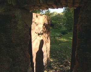Slightly open door in ancient wall and shadow walking away.