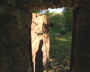 Slightly open door in ancient wall and shadow walking away.