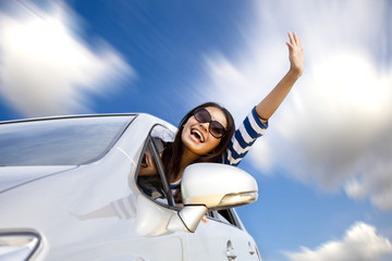 happy young woman in car driving on the road
