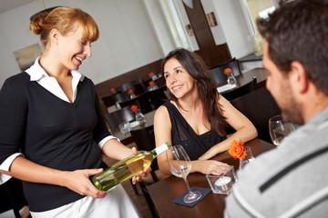 Kellnerin schenkt Frau Wein ein