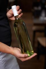 Weinkellner hält Weinflasche im Restaurant