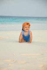 Happy kid crawling on the beach
