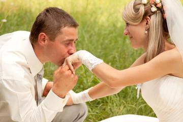 Caucasian prime adult male groom kissing hand of female bride