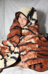 Young smiling girl wrapped in a blanket
