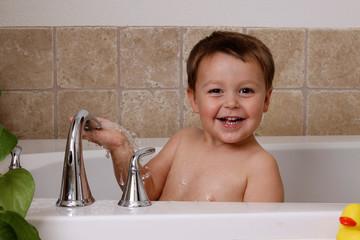 little boy playing in the bathtub