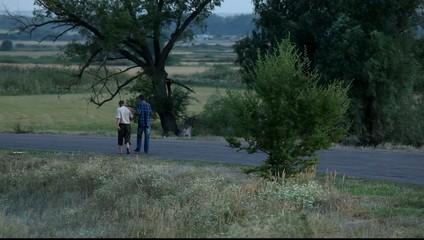 Два человека в сумерках идут по дороге.