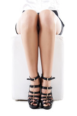 Young woman's legs in fashionable high heel black shoes, on whit