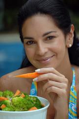 Mujer comiendo ensalada en la piscina.