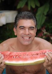 Hombre comiendo sandia fresca.
