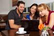 Lachende Freunde mit Netbook und Smartphone