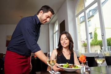 Freundlicher Kellner bringt Salat