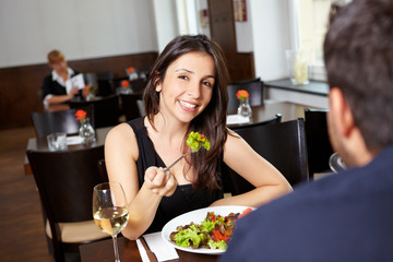 Frau mit Salat lacht im Restaurant