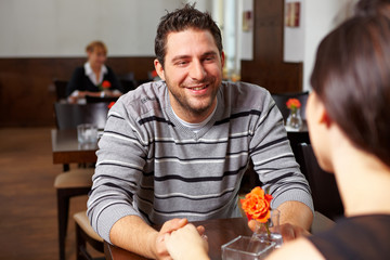 Mann im Restaurant hält Hände einer Frau