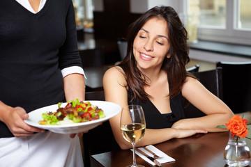 Frau schaut auf Salat im Restaurant