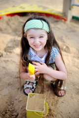 Happy child girl wearing green headband plays in a sandbox