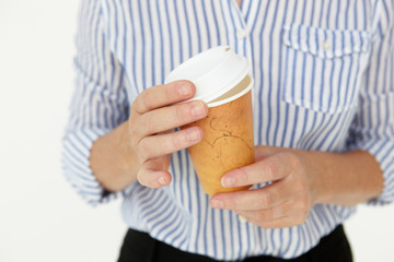 Businesswoman holding takeout coffee