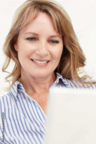 Mid age businesswoman using laptop